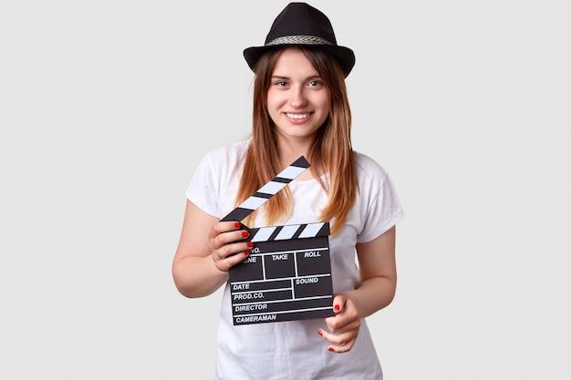 Productor de cine sonriente sostiene claqueta