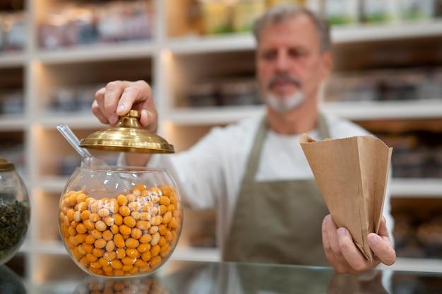 Productor en su tienda con alimentos frescos.