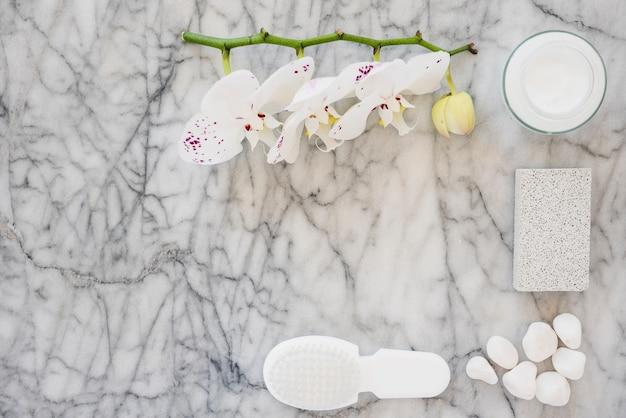 Productos de baño blancos sobre superficie de mármol.