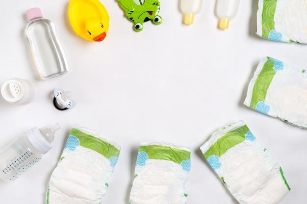 Productos para bebés aceite de champú en crema para bebés en pañales sobre fondo blanco con espacio de copia vista superior o fl ...