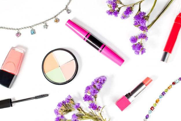Productos de belleza y joyas sobre un fondo blanco.