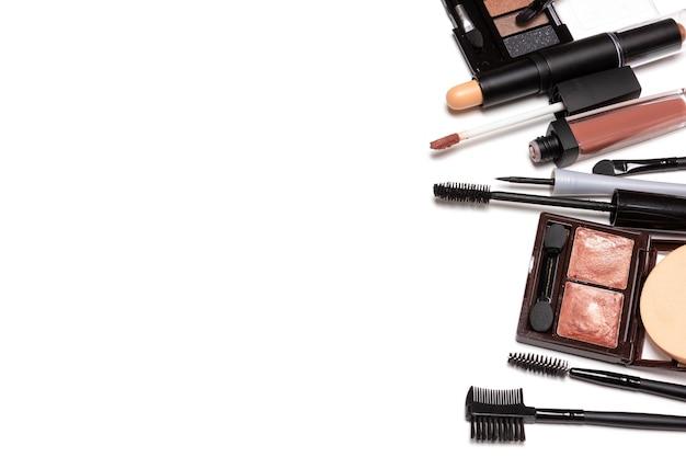Productos de belleza para el maquillaje diario informal sobre fondo blanco. marco lateral, espacio de copia
