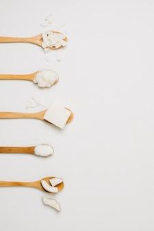 Productos de coco en cucharas de madera con espacio de copia