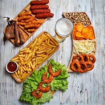 Productos de comida chatarra con cerveza, queso, barbacoa, pistacho en platos de madera.