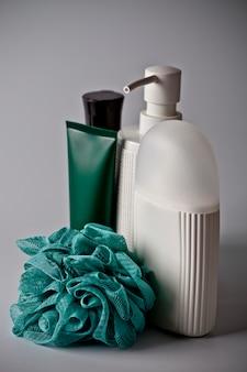 Productos cosméticos para el baño: jabón líquido, espuma de baño, crema y esponja turquesa.