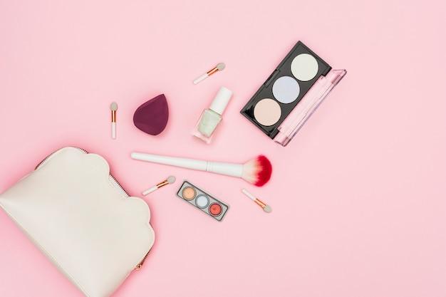 Los productos cosméticos se derramaron de la bolsa de maquillaje sobre fondo rosa