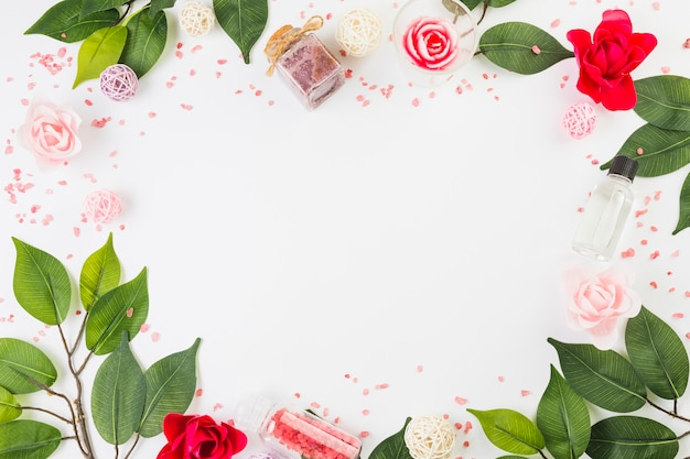 Productos cosméticos y hojas formando marco sobre superficie blanca.