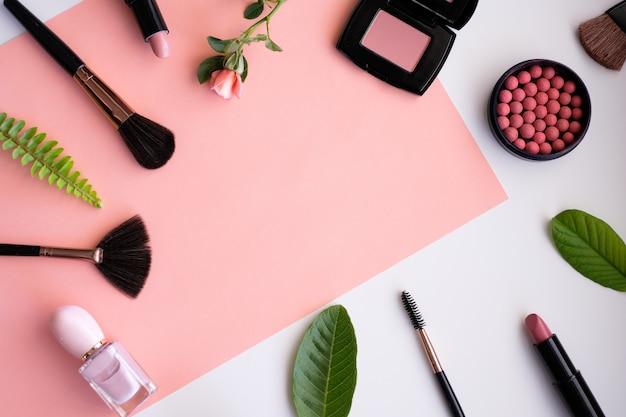 Productos cosméticos de maquillaje con hojas de naturaleza sobre fondo rosa.