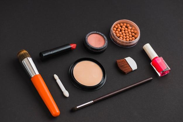 Productos cosméticos y pinceles de maquillaje sobre fondo negro
