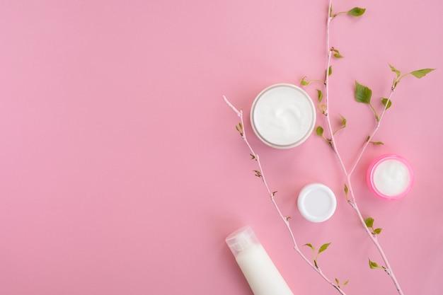 Productos cosméticos y rama con hojas verdes. concepto de belleza y cuidado de la piel
