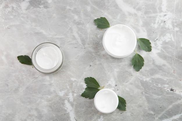 Productos de crema corporal laicos planos sobre fondo de mármol