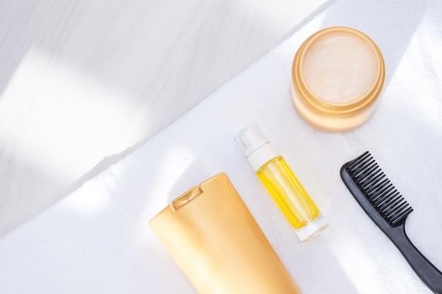 Productos para el cuidado del cuerpo y el cabello, artículos de tocador con toalla, luz solar. concepto de cuidado y limpieza para la piel, el cabello y el cuerpo. lay flat, copia espacio.