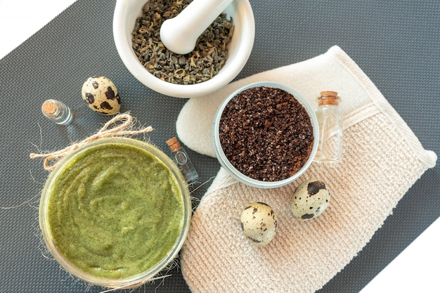 Los productos para el cuidado del cuerpo se colocan planos con té, sal, café, aceite natural y huevos de codorniz. spa bodegón. peeling corporal.