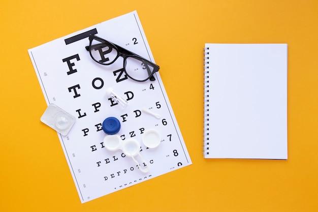 Productos para el cuidado de los ojos con maqueta de cuaderno sobre fondo naranja