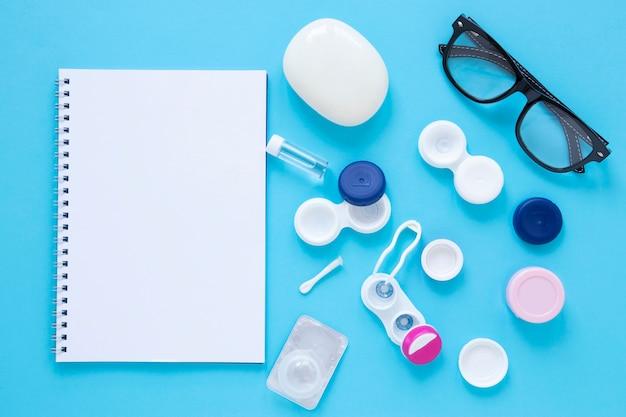 Productos para el cuidado de los ojos sobre fondo azul con maqueta de cuaderno