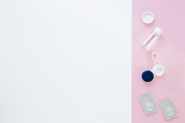Productos para el cuidado de los ojos sobre fondo rosa y blanco