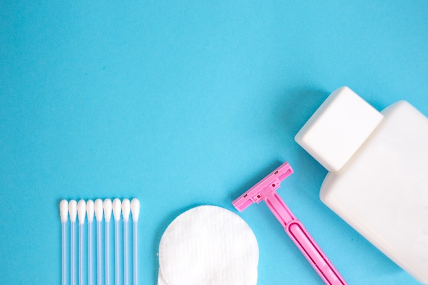 Productos de cuidado personal vista superior. botella blanca, maquinilla de afeitar, palillos para las orejas, almohadillas de algodón en la parte posterior azul
