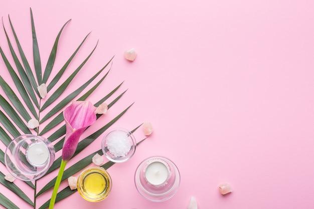 Productos para el cuidado de la piel en una rama de palma