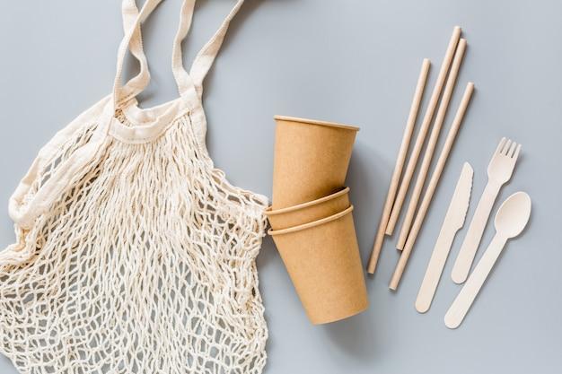 Productos ecológicos blancos y bolsa de hilo sobre papel gris