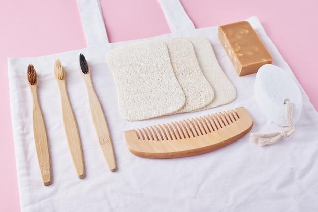 Productos ecológicos de madera natural para el cuidado del cuerpo sobre un fondo rosa, vista superior plana.