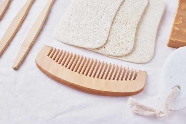 Productos ecológicos de madera naturales para el cuidado del cuerpo en rosa, vista superior plana, cepillos de dientes de bambú, peine de madera, jabón, esponjas y paños naturales, concepto de cero residuos