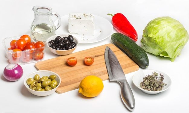 Productos para ensalada griega sobre un fondo blanco.