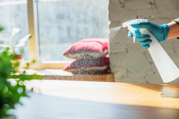 Productos esenciales durante la epidemia: prevención y protección de la propagación del coronavirus covid-19. mano en guantes desinfectando superficies con desinfectante en casa. limpieza contra el virus de la neumonía.