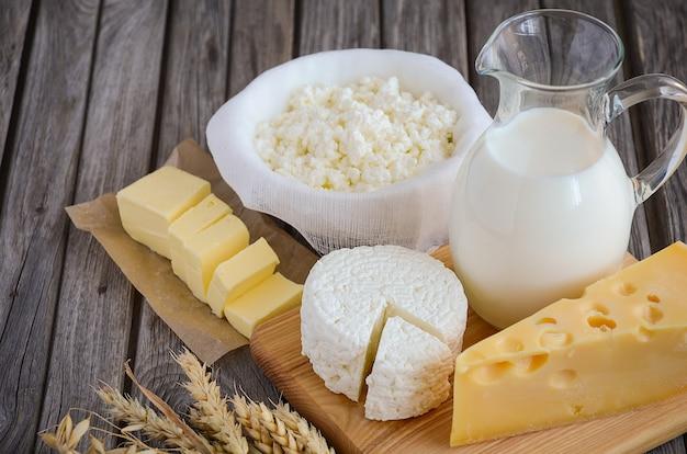 Productos lácteos frescos. leche, queso, mantequilla y requesón con trigo en el fondo de madera rústica.