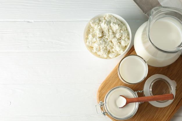 Productos lácteos frescos, tablero y toalla en la mesa de madera blanca