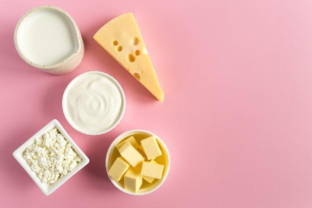 Productos lácteos de leche mantequilla queso leche sobre papel rosa