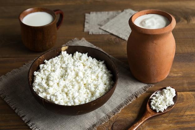 Productos lácteos requesón, leche, crema agria de cerca en platos de barro y madera en una servilleta de lona sobre un fondo de madera oscura.
