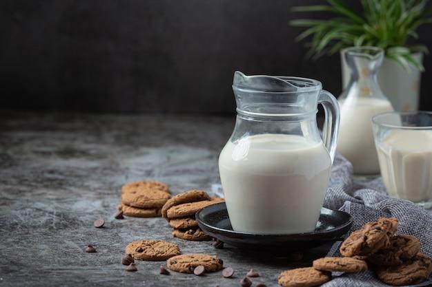 Productos lácteos sabrosos productos lácteos saludables en una mesa de crema agria en un tazón, tazón de requesón, crema en un banco y tarro de leche, botella de vidrio y en un vaso.