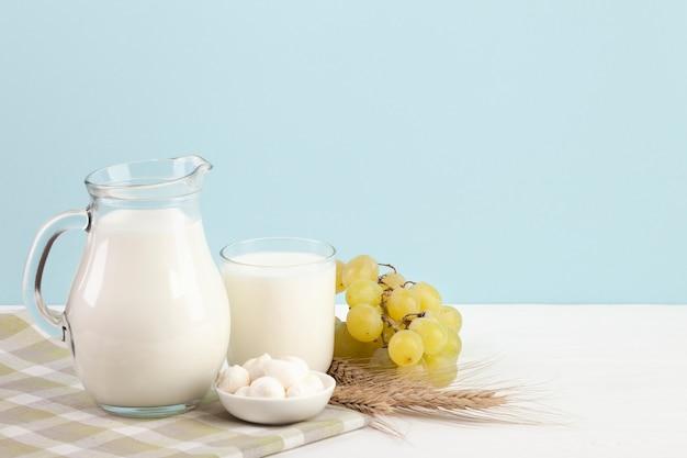 Productos lácteos y uvas en mesa.