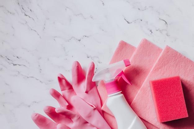 Productos de limpieza y desinfección en colores rosa sobre fondo de mármol vista superior copia espacio.