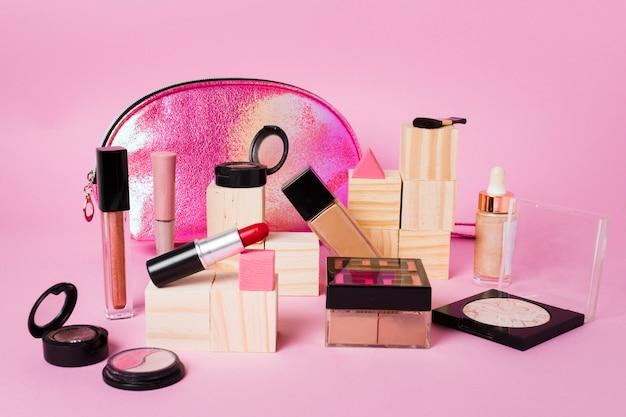 Productos de maquillaje y bolsa de cosméticos brillante sobre fondo rosa