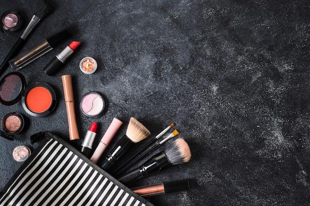 Productos de maquillaje y bolso cosmético a rayas sobre fondo oscuro polvoriento.