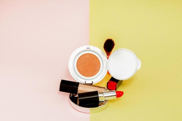 Los productos de maquillaje se derraman sobre un fondo amarillo y rosa brillante con espacio de copia