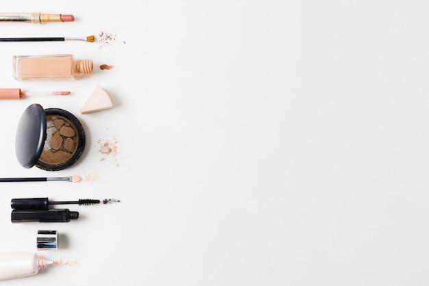 Productos de maquillaje dispuestos sobre fondo gris.