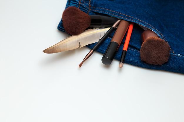 Productos de maquillaje y productos de belleza estética que se derraman desde los vaqueros de mujer.