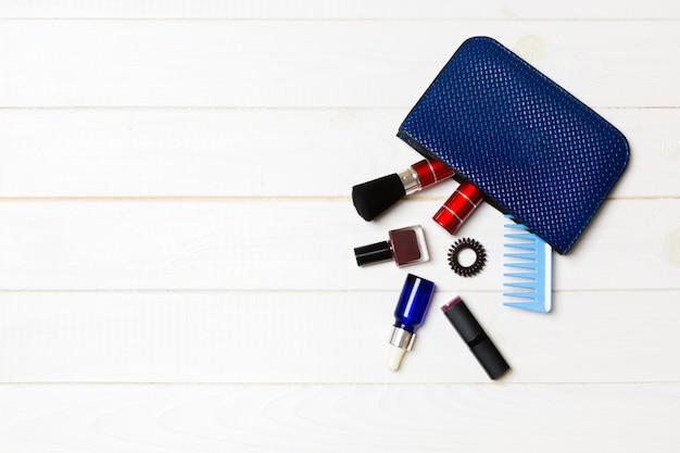 Productos de maquillaje que se derraman de la bolsa de cosméticos en madera blanca