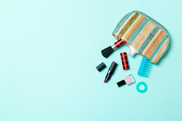 Productos de maquillaje que se derraman de la bolsa de cosméticos, sobre fondo azul pastel