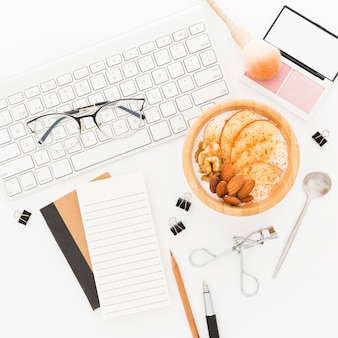 Productos de maquillaje y tazón con yogurt en el escritorio