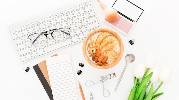 Productos de maquillaje y tazón con yogurt en la oficina