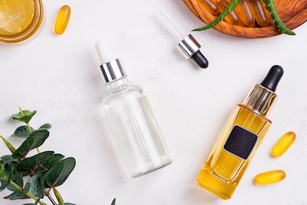 Productos naturales de belleza con crema cosmética, cápsulas de gel omega 3 y suero en frascos de vidrio en blanco.