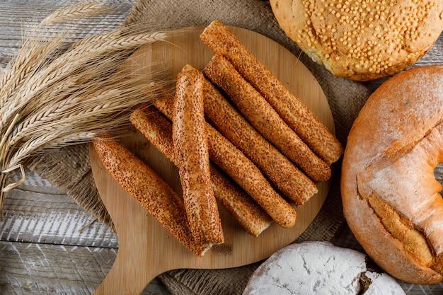 Productos de panadería con vista superior de cebada en una tabla de cortar y superficie de madera