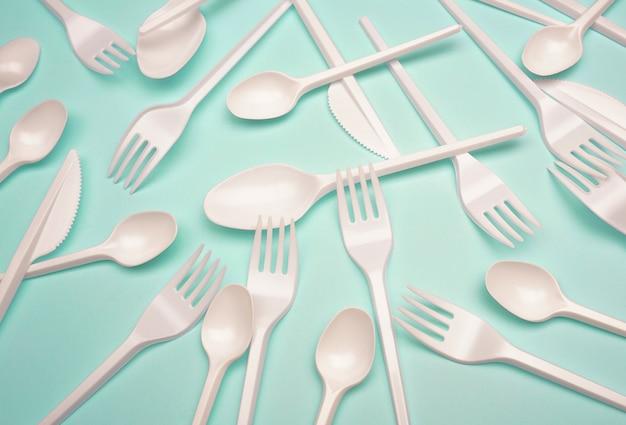 Productos de plástico de un solo uso: cubiertos de plástico, tazas sobre fondo azul brillante