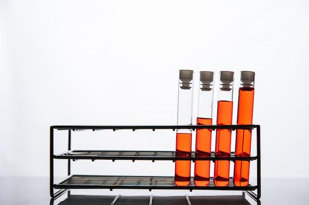 Productos químicos de color naranja en un tubo de vidrio de ciencia dispuestos en un estante