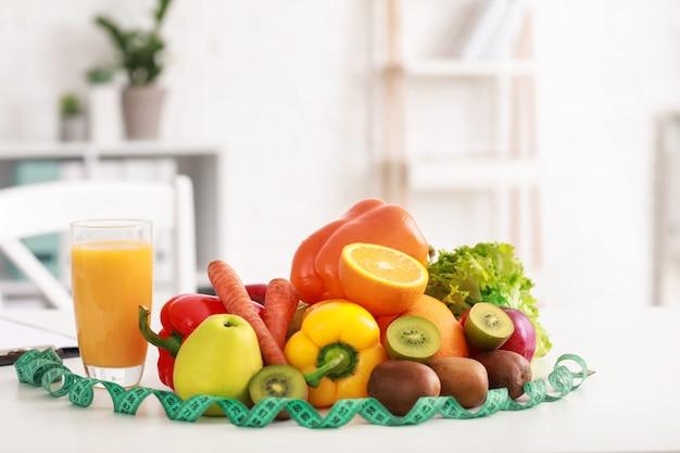 Productos saludables y cinta métrica en la mesa en la oficina del nutricionista