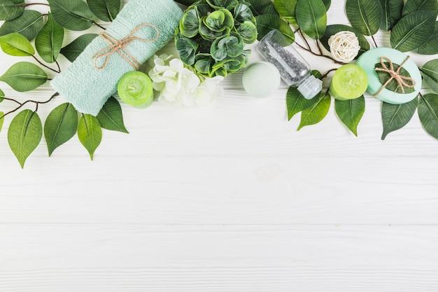 Productos de spa decorados con hojas verdes sobre superficie de madera.