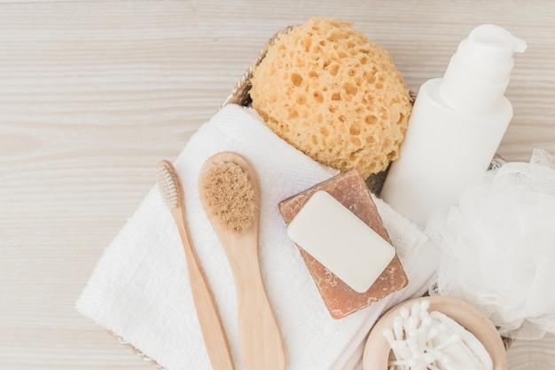 Productos de spa con pinceles y lufa sobre fondo de madera.